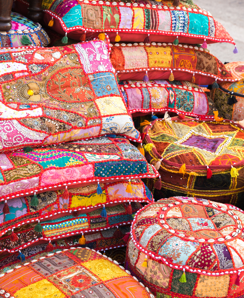 Colorful handmade pillows and ottomans embellished with local shells for sale at a market in Abu Dhabi.