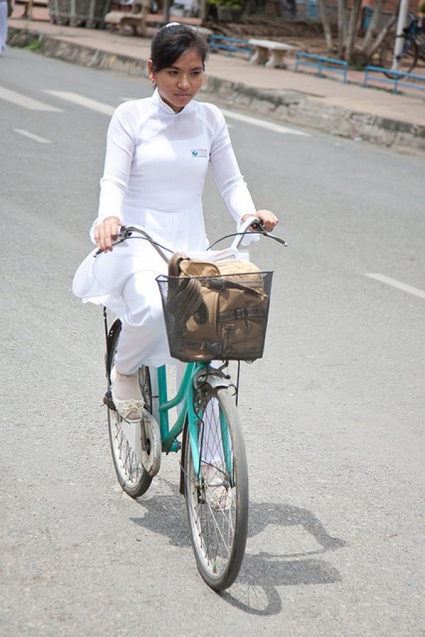 A uniformed teacher bicycles home after school.