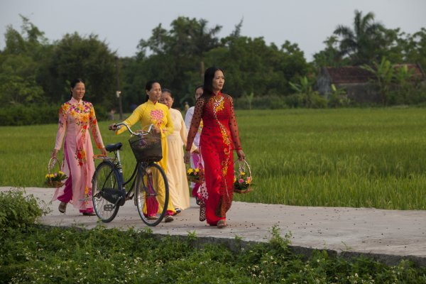 Women in traditional Ao Dai dress walk to church in Ninh Binh.