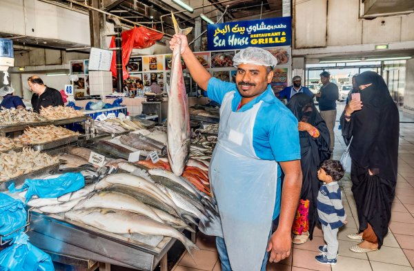 A fisherman showing off the catch of the day at Al Mina fish market in Abu Dhabi
