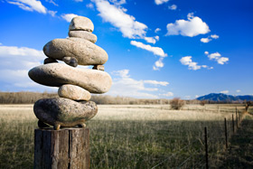 Balancing stones on a fencepost in Big Sky Country