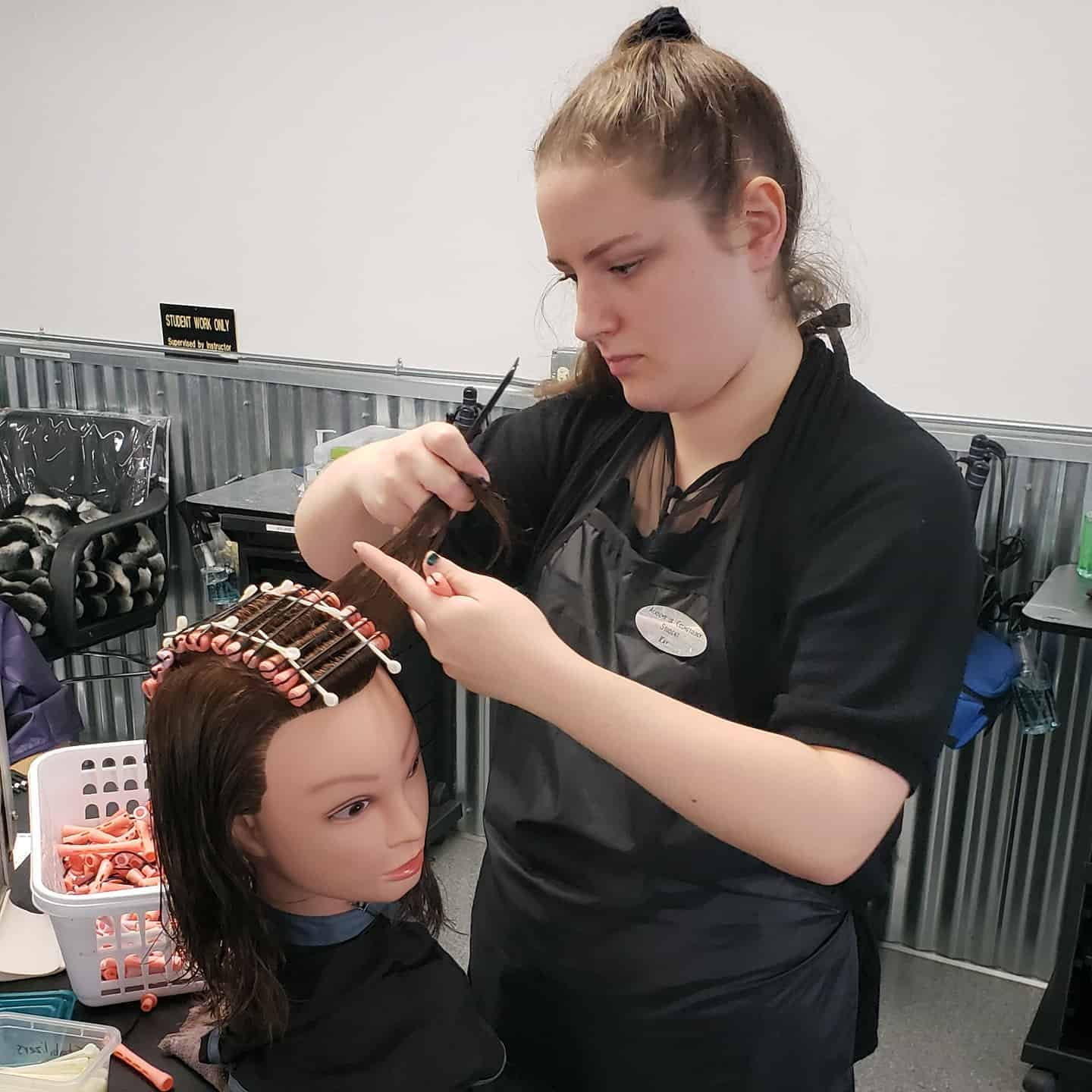 A student learns to perm hair at Academy of Cosmetology in Bozeman.